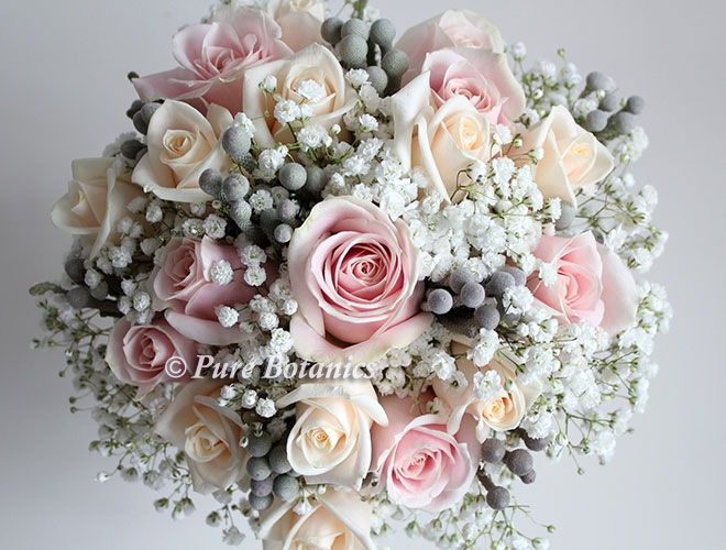 Pale pink and cream roses arranged in a psoy bouquet with ivory gypsophila flowers.