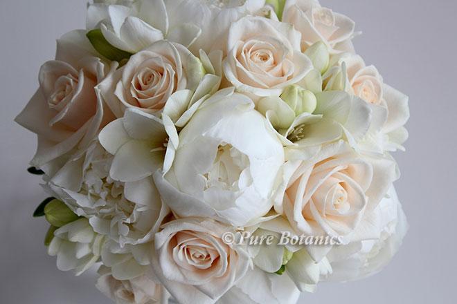 Ivory peonies and cream roses arranged in a posy bouquet.