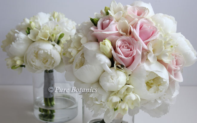White peonies arranged with roses and freesias to create spring wedding bouquets.