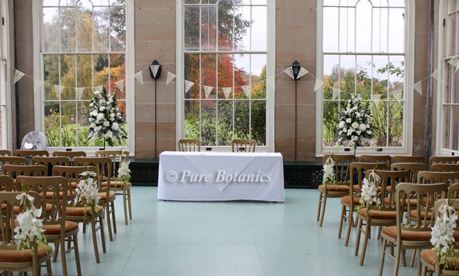 The orangery at Stoneleigh Abbey decorated with white wedding ceremony flowers.
