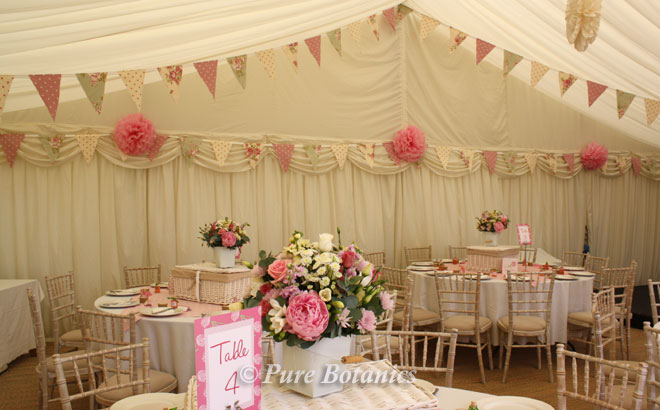 Pink and ivory peonies, roses and stocks arranged in pails for a summer garden wedding.