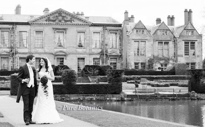Bride holding her shower bouquet in the grounds of Coombe Abbey.