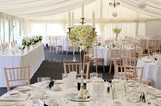 Candelabras decorated with white wedding flowers at Wethele Manor Nr Leamington Spa.
