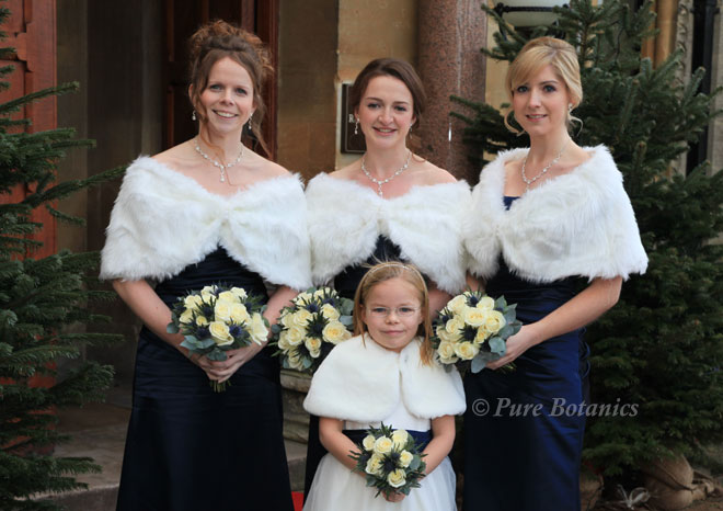 Ivory roses and blue thistle bouquets for a navy blue wedding colour theme.