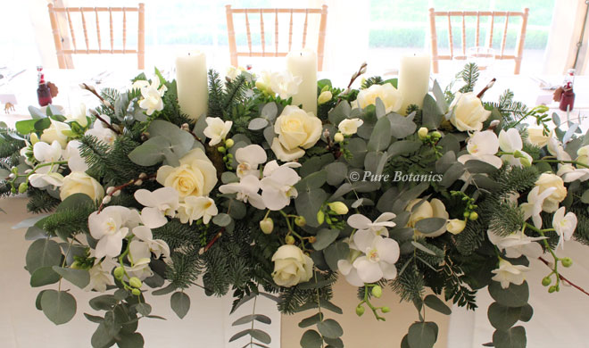 Roses, orchids, eucalyptus arranged around large church candles for a top table arrangement.