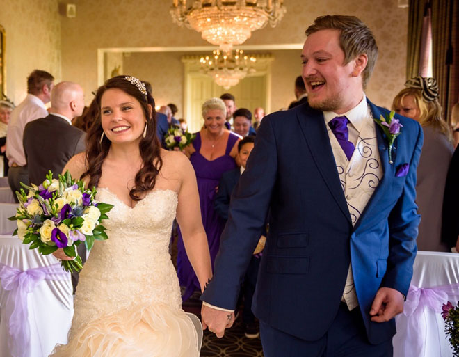 Bride carrying a handtied posy bouquet in ivory and purple with the groom at Walton Hall.