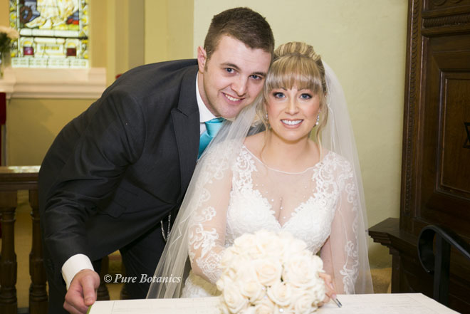 Bride and groom signing the register in St James chapel in Walton, Warwickshire.