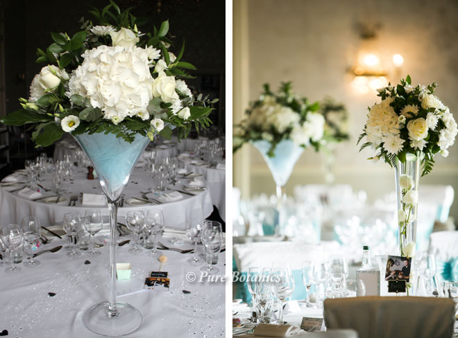 Tall blue and ivory wedding centrepieces featuring roses and hydrangeas.