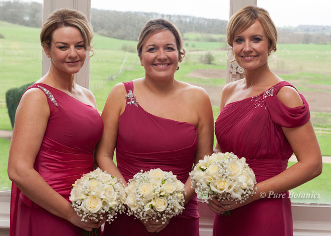 Bridesmaids holding bouquets of roses, gypsophila and freesias.