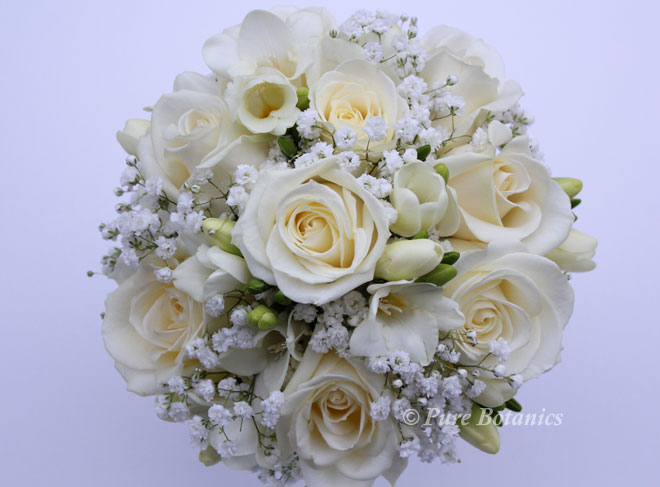Posy bridal bouquet in ivory featuring roses, gypsophila and freesias.