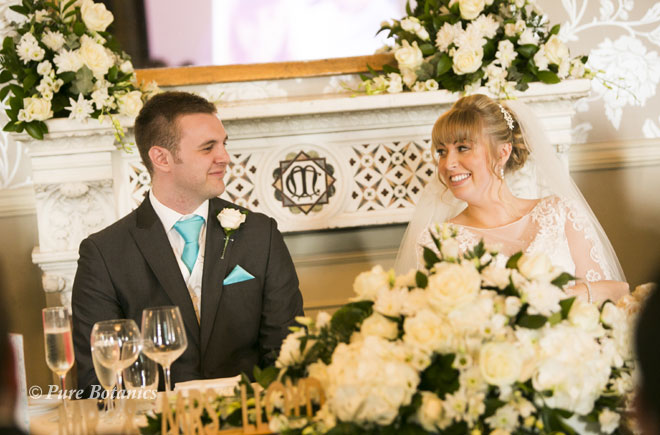Top table wedding flowers featuring ivory roses and white hydrangeas.
