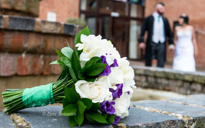 Bridal posy bouquet featuring ivory roses, freesias and purple lisianthus.