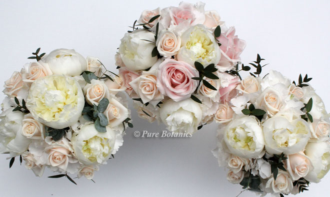 Blush pink and cream roses arranged with peonies and hydrangeas for summer bridal bouquets.