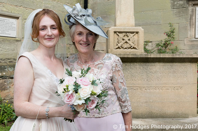The bride and her mum photographed outside the church holding her rose posy bouquet.