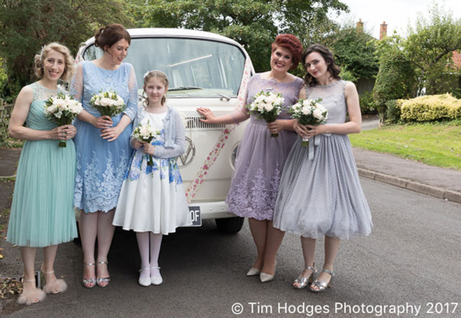 Bridesmaids in muted pastel tones arriving at the church in a VW camper van.