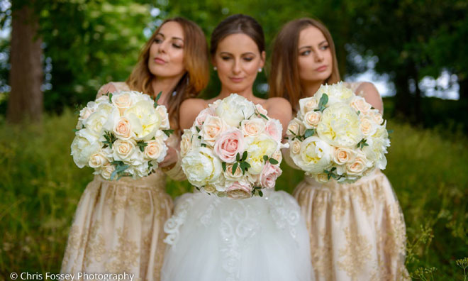 Bride and bridesmaids holding handtied posy bouquets of roses peonies and hydrangeas.