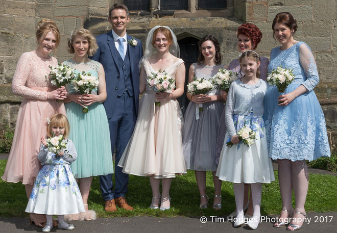 Wedding party photographed with the flower bouquets outside the church.