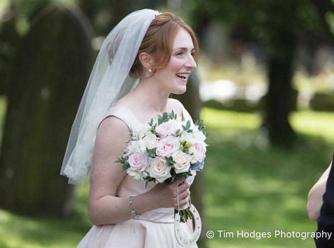 Bride holding a pastel flower bouquet in the church grounds in Leamington Spa.