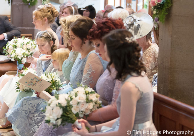Bridal bouquets being held by the bride and bridesmaids in the church wedding ceremony.