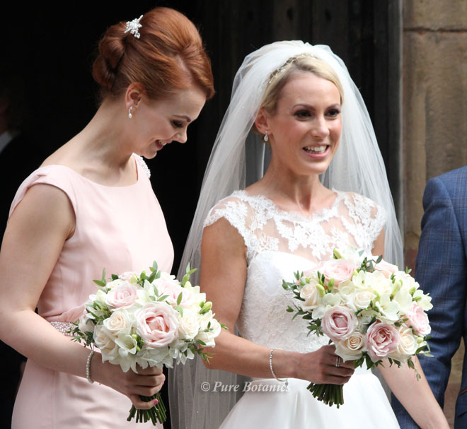 Bride and bridesmaid outside the church with their bridal bouquets.