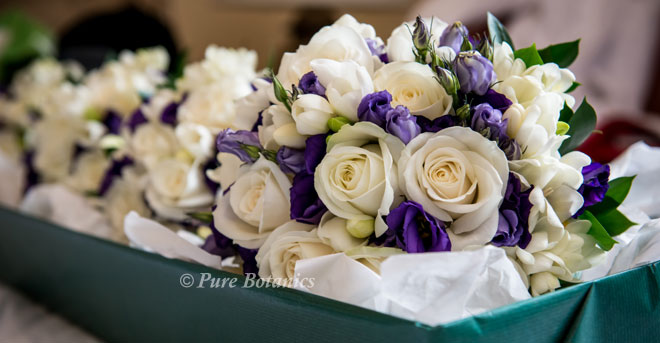 Ivory rose, freesia and purple lisianthus bridal bouquets boxed ready for delivery to Stratford Upon Avon.