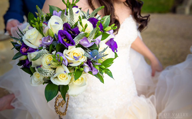 Bridal bouquet featuring ivory roses, lilac freesias and purple lisianthus.