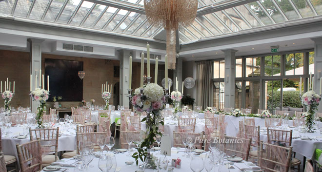 Candelabra wedding centrepieces decorated with roses and hydrangeas at Hampton Manor.