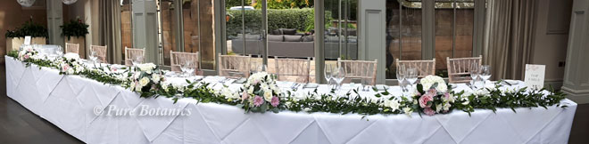 Flower clusters linked with ruscus and Singapore orchids to form a top table garland.