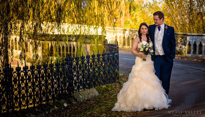 Wedding couple photographed on the bridge at Walton Hall, Wellesbourne.