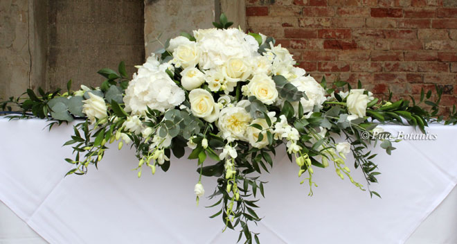 White spring wedding flowers on the ceremony table for an outdoor wedding at Ettington Park hotel.