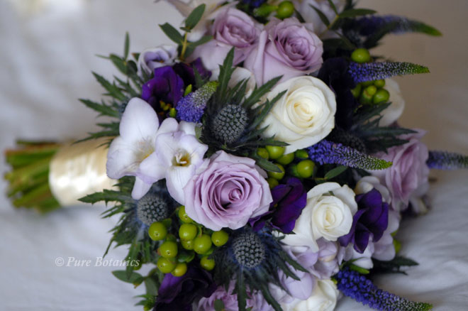 Bridal posy bouquet featuring roses, freesias, thistle hypericum and lisianthus.