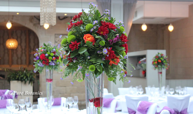 Red and orange roses in a tall wedding table decoration at Hampton manor.