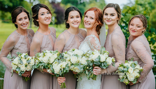 Bride and bridesmaids photographed with their posy bouquets in ivory.