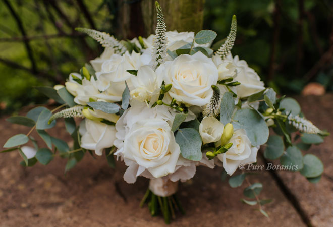 White crescent shaped posy bouquet featuring roses, freesias and eucalyptus.