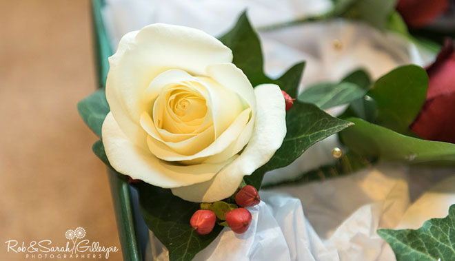 Rose buttonhole with red berries for a winter wedding.