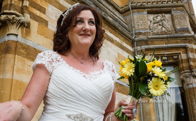 Bride with a posy bouquet for a yellow wedding colour theme.